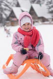 Little girl sitting on sledges Royalty Free Stock Photography