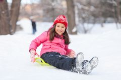 Little girl sitting on sledges and sliding. Stock Photo