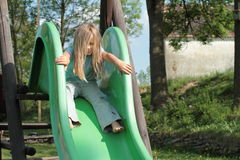 Little girl sitting on a slide Royalty Free Stock Image