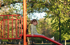 Little girl sitting on slide Royalty Free Stock Photo