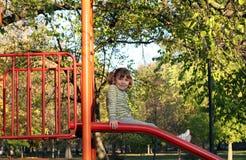 Little girl sitting on slide Royalty Free Stock Photo