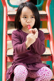 Little girl sitting on the slide. And eating a lollipop Stock Photos