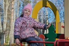 Little girl sitting on the slide at the Playground and smiles. Looking at us and holding his hand over the wooden fir. Day, the sun shining in the background Royalty Free Stock Photo