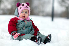 Little girl sitting in snow Stock Photos
