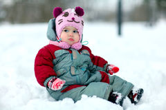Little girl sitting in snow Stock Image