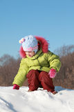 Little girl sitting at snow outdoors Stock Photo