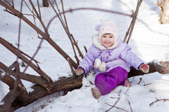 Little girl sitting in snow, walk Royalty Free Stock Images