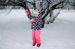A little girl sitting on snow in winter park Stock Photography