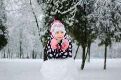 A little girl sitting on snow in winter park Royalty Free Stock Photos