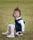 Little girl sitting on a soccer ball. Royalty Free Stock Images