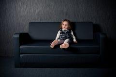 Little girl sitting on sofa Stock Images