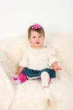 Little girl sitting on a sofa Stock Photos
