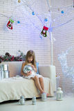 Little girl sitting on the sofa with Christmas gifts and playing Stock Photo