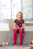 Little girl sitting on sofa's back-rest smiling Royalty Free Stock Image