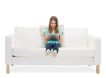Little girl sitting on sofa with tablet pc comuter Stock Images