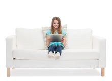 Little girl sitting on sofa with tablet pc comuter Stock Photography
