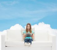 Little girl sitting on sofa with tablet pc Stock Image