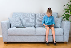 Little girl sitting on sofa and using tablet pc. Stock Photo