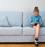 Little girl sitting on sofa and using tablet pc. Royalty Free Stock Photos