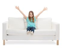 Little girl sitting on sofa and waving hands Royalty Free Stock Photo