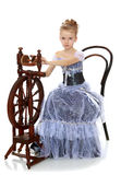 Little girl sitting at a spinning wheel. Royalty Free Stock Photo