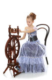 Little girl sitting at a spinning wheel. Stock Image