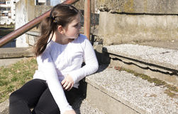 Little girl sitting on a stairs. In a city park Stock Image