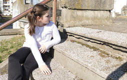 Little girl sitting on a stairs. In a city park Royalty Free Stock Photos