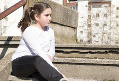 Little girl sitting on a stairs. In a city park Royalty Free Stock Photo