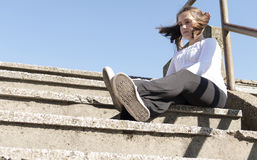 Little girl sitting on a stairs. In a city park Royalty Free Stock Images