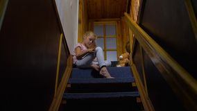 Little girl sitting on stairs. Sitting on stair home with brown teddy bear interior indoors house child little girl female. caucasian white european 5 years old stock footage
