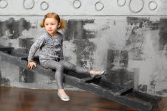 Little girl sitting on a stairs Stock Photo