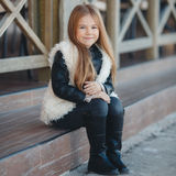 Little girl sitting on the steps near the house. Stock Photography
