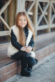Little girl sitting on the steps near the house. Stock Image