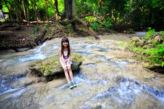 Little girl sitting on stone. In a forest stream Royalty Free Stock Image