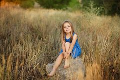 Little girl sitting on stones royalty free stock photography