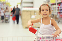 Little girl sitting in store cart Stock Images