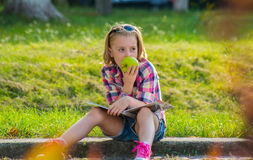 Little girl sitting on the street eating an apple. Royalty Free Stock Photos