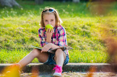 Little girl sitting on the street eating an apple. Royalty Free Stock Photography