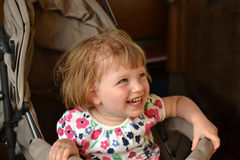 Little girl is sitting in stroller and laughs Royalty Free Stock Photos