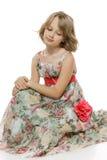 Little girl sitting on the studio floor Royalty Free Stock Photo