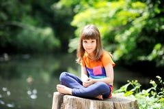 Little girl sitting on stump Royalty Free Stock Photos
