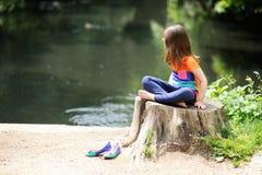 Little girl sitting on stump Stock Photos