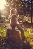 Little girl sitting on the stump in the forest Stock Photo
