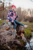 A little girl is sitting on a stump near a stream. Royalty Free Stock Photography