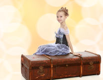 Little girl sitting on a suitcase. Beautiful little girl in a long Princess dress , sitting on an old road suitcase Stock Images
