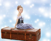 Little girl sitting on a suitcase. Beautiful little girl in a long Princess dress , sitting on an old road suitcase.Blue Christmas festive background with white Royalty Free Stock Photo