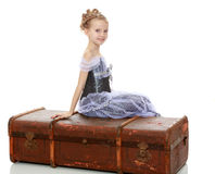 Little girl sitting on a suitcase. Beautiful little girl in a long Princess dress , sitting on an old road suitcase.Isolated on white background Stock Photography