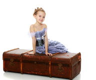 Little girl sitting on a suitcase. Beautiful little girl in a long Princess dress , sitting on an old road suitcase.Isolated on white background Royalty Free Stock Photos