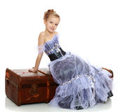 Little girl sitting on a suitcase. Beautiful little girl in a long Princess dress , sitting on an old road suitcase.Isolated on white background Stock Image